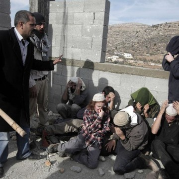 Image: A Palestinian man (L) from the village of Qusra protects a group of Israeli settlers