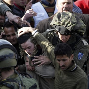 Image: Palestinians hit an Israeli settler, center.