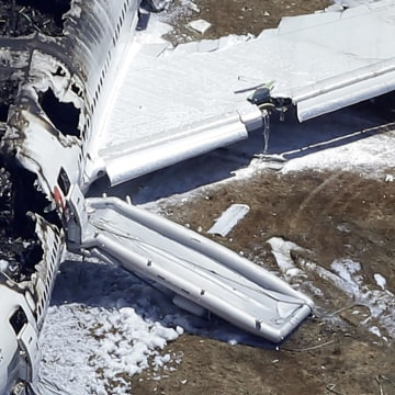 Image: A firefighter stands by a tarpaulin sheet covering a body near the wreckage of the Asiana Flight 214