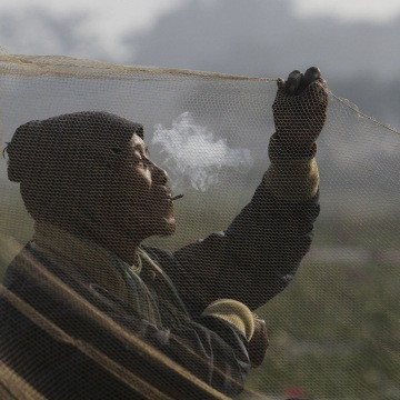 Image: An Indian villager smokes and arranges his fishing net during Bhogali Bihu celebrations
