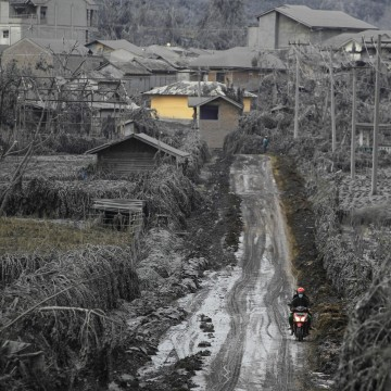 Image: A villager rides a motorcycle through a road covered with mud from a Mount Sinabung eruption at Kuta Rakyat village in Karo district