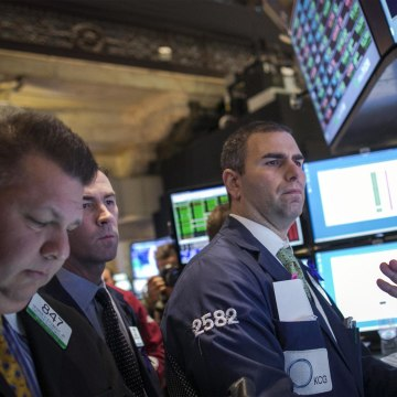 Traders work on the floor of the New York Stock Exchange on Tuesday where the Dow ended 115 points higher