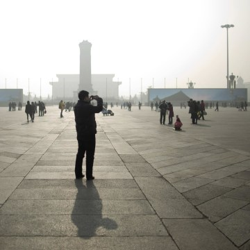 Image: A tourist takes photos during a heavily polluted day on Tiananmen Square in Beijing.