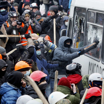 Image: Pro-European protesters attack a police van during a rally near government administration buildings in Kiev