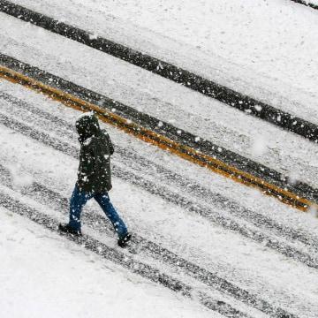 Image: A pedestrian walks through the falling snow in Medford