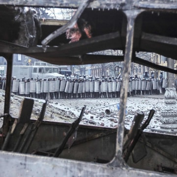 Image: Ukrainian riot police take cover behind their shields in front of a burnt bus during a rally near government administration buildings in Kiev