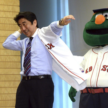 Image: Japan's PM Abe smiles as he wears a jersey of Boston Red Sox, while Red Sox mascot Wally looks on at Abe's office in Tokyo
