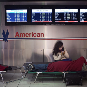 Image: A woman sits on her cot at John F. Kennedy International Airport in New York