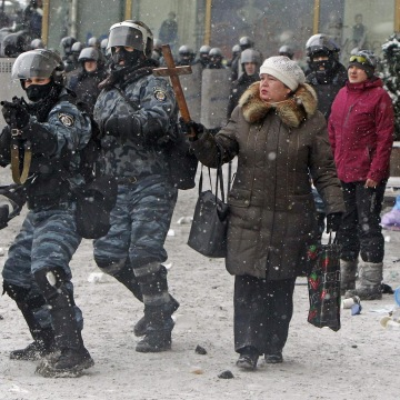 Image: A woman holds a wodden cross as riot policemen aim their weapons during clashes with pro-European protesters in Kiev