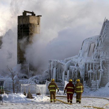 Image: Firefighters walk past the Residence du Havre after a fire in L'Isle Verte, Quebec