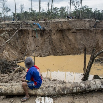 Image: A child looks at the tailing produced by illegal gold mining