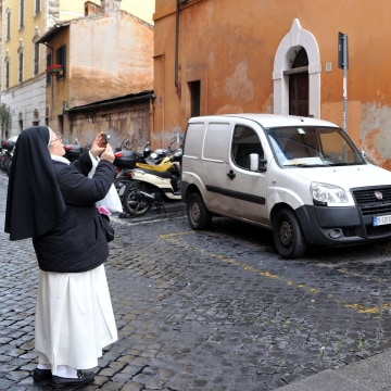 Image: A nun takes a picture of a street art mural of Pope Francis as a superman.