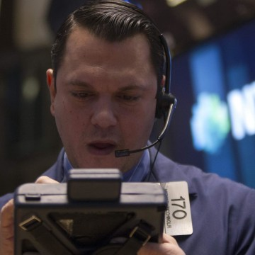 Trader works on the floor of the New York Stock Exchange on Wednesday. The Dow fell almost 200 points as the Federal Reserve said it will cut another $10 billion from its stimulus package.
