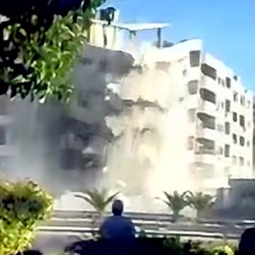 A video screenshot shows government soldiers and civilian contractors overseeing the demolition of a seven story residential apartment building with controlled explosions in the Zahirat neighborhood of Damascus. Video recorded late September 2012.