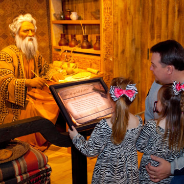 Image:  Sisters Bella, 5 and Laura Katherine Coker 3, of Jackson, Miss tour the Creation Museum in Petersburg, Ky with their father John Coker. One of the animatronic displays allows visitors to ask question of Noah including one that explains how dinosau