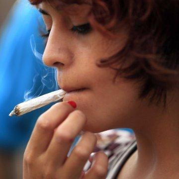 A young woman using a marijuana cigarette