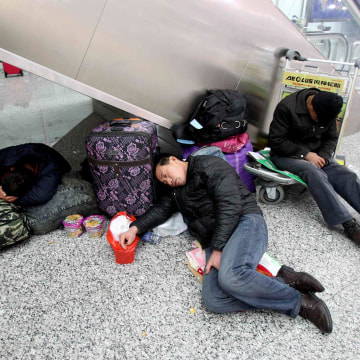 Image: Passengers sleep on their luggages after being stranded due to heavy snowfall at the Zhengzhou Xinzheng International Airport in Zhengzhou