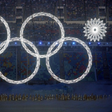 Image: Performers sing as the Olympic rings are presented during the Opening Ceremony of the Sochi Winter Olympics at the Fisht Olympic Stadium