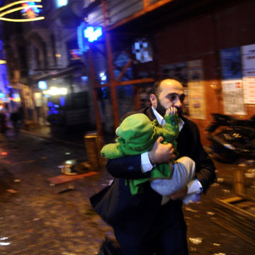 Image: A man carrying a baby runs away from tear gas