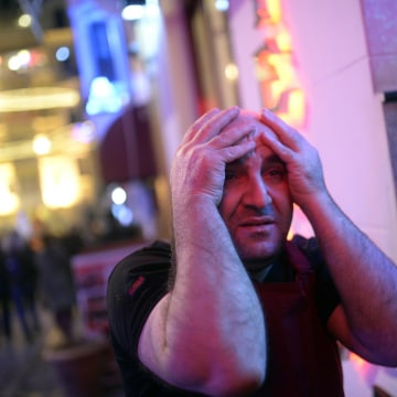 Image: A shop owner holds his head in reaction to a protest
