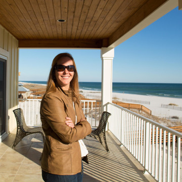 Image: Realtor Erin E. Kaiser stands on a deck of a house she owns in Gulf Shores, Ala.
