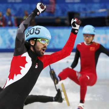 Image: Canada's Charles Hamelin celebrates winning as China's Chen Dequan and J.R. Celski of the U.S. fall, during the men's 1,500 metres short track speed skating race finals at the Iceberg Skating Palace during the 2014 Sochi Winter Olympics