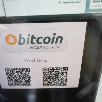 A bitcoin logo is seen at the window of a restaurant that accepts bitcoin.