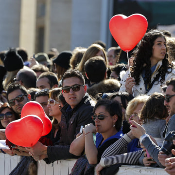 Image: Faithful hold heart-shaped balloons as Pope Francis leads a special audience with engaged couple, to celebrate Saint Valentine's day, in Saint Peter