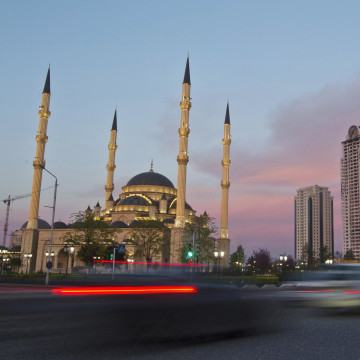 Cars drive along Akhmad Kadyrov Avenue, with the Heart of Chechnya mosque and skyscrapers in the background