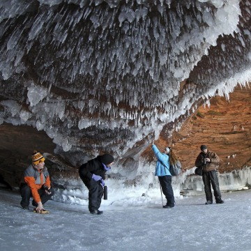 Image: Sightseers crouch to avoid icicles in a sea cave on frozen Lake Superior at the Apostle Islands National Lakeshore
