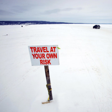 Image: Car travels the ice road on Lake Superior between Bayfield, Wisconsin and Madeline Island