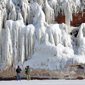 Image: Sightseers look at a frozen rock face along the Apostle Islands National Lakeshore of Lake Superior