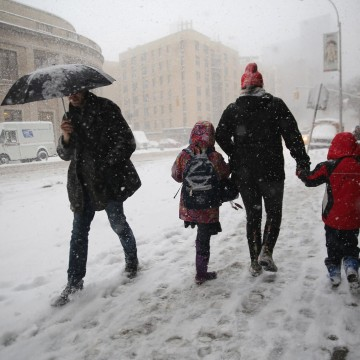 Image: A person walks two kids to school during a snowstorm
