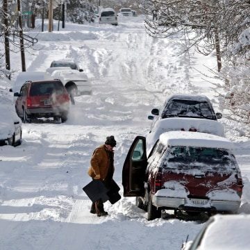 Image: A man clears snow from his car in Indianapolis, Ind.