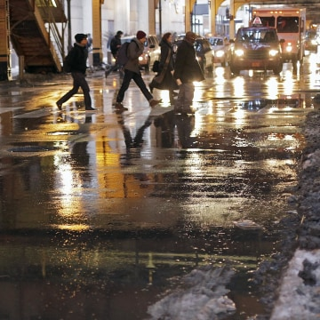 Image: Evening commuters navigate melting snow and puddles Tuesday as they head home in Chicago.