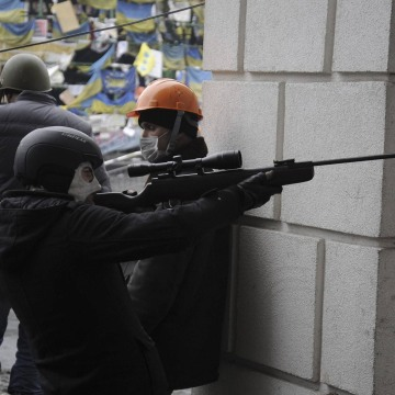 Image: An anti-government protester aims a rifle during clashes with riot police in Independence Square in Kiev