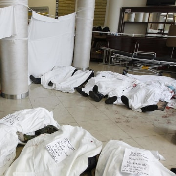 Image: A priest stands in the lobby of the hotel Ukraine near bodies of anti-government protesters killed during clashes with riot police in Kiev