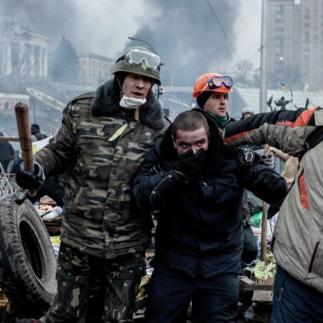 Image: Anti-government demonstrators escort a captured police officer in Kiev