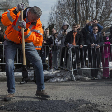 New York Mayor Bill de Blasio finishes filling a pothole in the Maspeth section of Queens.