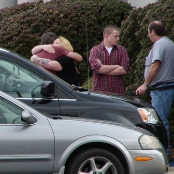 Image: People hug outside a memorial for 17-year-old Christopher Roupe