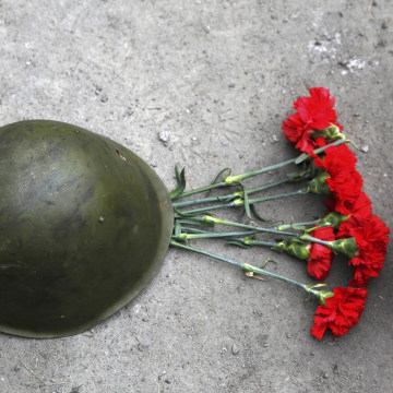 Image: Roses are placed under a combat helmet during a funeral service for two anti-governent protesters who were killed after days of violence in Kiev