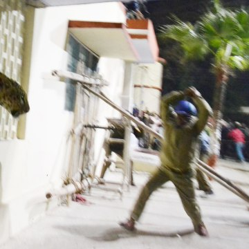 Image: A leopard squeezes through a hole in the wall of the Meerut Cantonment Hospital as an official approaches in Meerut on February 23, 2014.