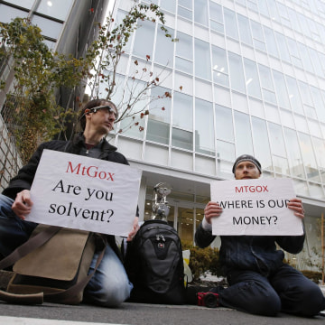 Protesters hold placards as they demonstrate against Mt. Gox in Tokyo