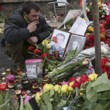 Image: A man mourns at a make-shift memorial for those killed in recent violence in Kiev