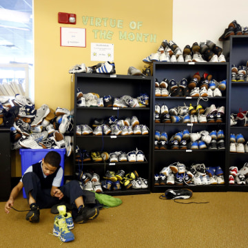 Image: Ramon Belliard, 10, puts his shoes on at the Lenfest Center