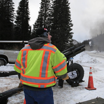 Image: A Colorado Department of Transportation employee uses an explosives launcher to try to trigger a controlled avalanche, near Empire, Colo.