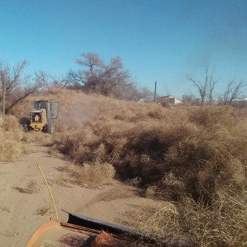 Snowplows attempt to clear a path to a rancher blockaded by piles of tumbleweeds in Crowley County, Colorado.