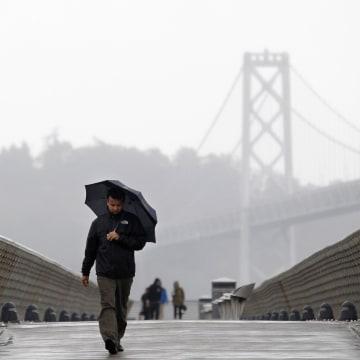 Image: A man walks down Pier 14 during a rain storm in San Francisco