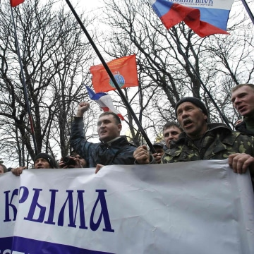 Image: People hold flags during a pro-Russian rally outside the Crimean parliament building in Simferopol