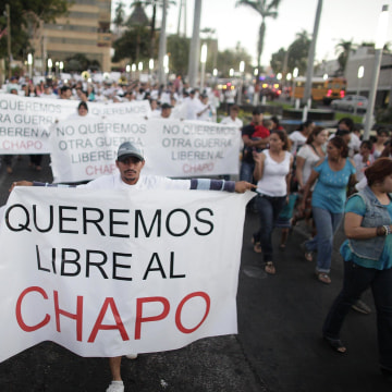 "Image: A protester holds a sign reading, ""We want Chapo free"" during a march in Culiacan"